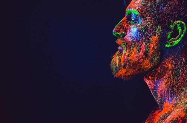 Concept. portret van een bebaarde man. de man is geschilderd in ultraviolet poeder.