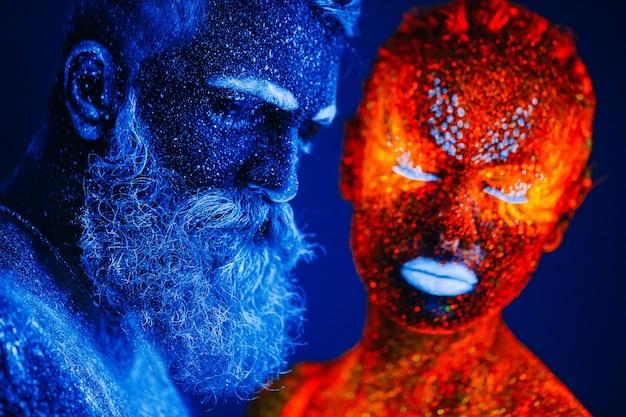 Concept. portret van een bebaarde man en vrouw geschilderd in ultraviolet poeder.