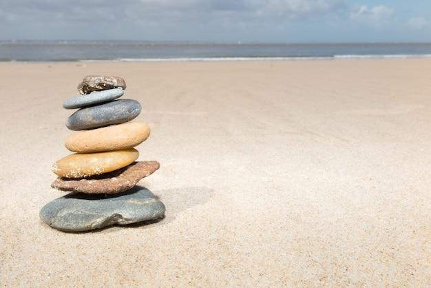 Concept stenensaldo en harmonie kiezelstenenstapel op het zandstrand overdag op een zonnige dag