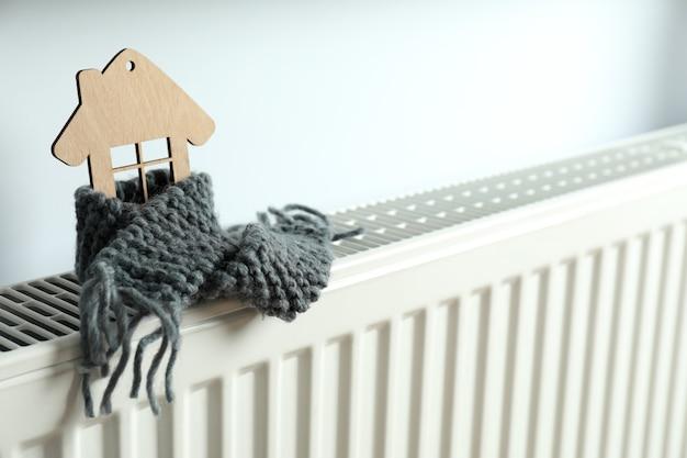 Concept stookseizoen met houten huis op verwarmingsradiator.