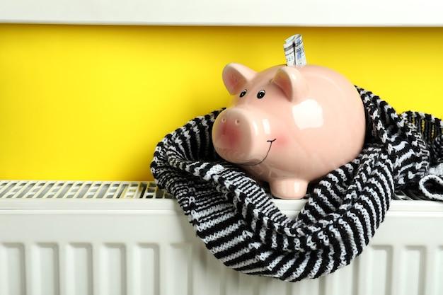 Concept stookseizoen met spaarvarken op radiator.