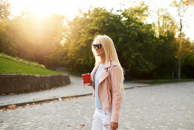 Concept straatmode. jonge stijlvolle studente wandelen in het zonnige park en houdt een kopje koffie te gaan.