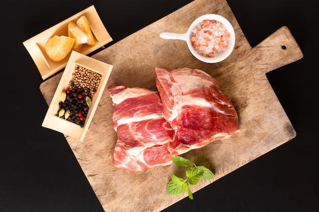 Concept stuk vlees zonder been varkensvlees kraag op snijplank met specerijen op zwarte achtergrond met kopie ruimte