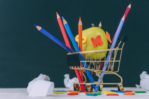 Concept terug naar school. groene appel met gekleurde letters en potloden om in een supermarktwagen te tekenen.