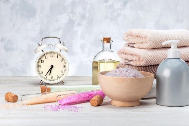 Concept, tijd om voor spa voor te bereiden. prachtige spa-compositie met wekker en natuurlijke cosmetica-producten.