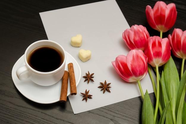Concept vakantie. boeket roze tulpen, een kopje koffie, hartvormige suiker, kaneel, steranijs en vel papier