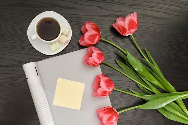 Concept vakantie. boeket roze tulpen, een kopje koffie