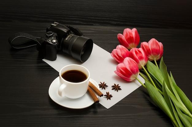 Concept vakantie. boeket van roze tulpen, dslr-camera, kopje koffie, kaneel, steranijs en vel papier