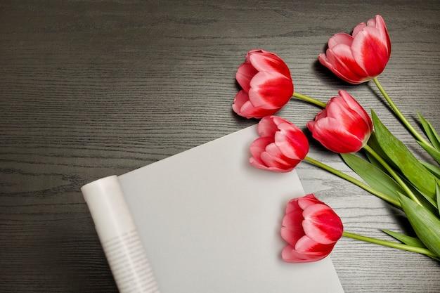 Concept vakantie. boeket van roze tulpen en stuk papier op zwart hout