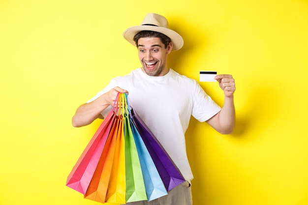 Concept vakantie en financiën. gelukkige mensenklant die tevreden boodschappentassen bekijkt, creditcard toont, die zich tegen gele achtergrond bevindt.