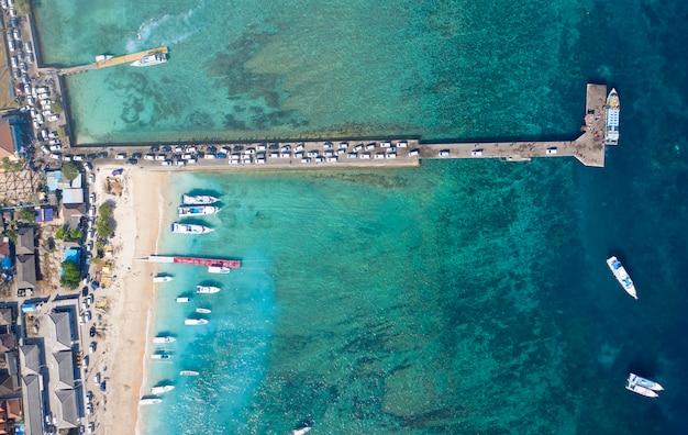 Concept vakantie. top-down drone van auto's die het eiland nusa penida binnenkomen via de haven van toya pakeh. bali, indonesië