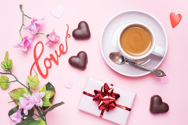 Concept valentijnsdag. chocoladesuikergoed en koffie, harten op een roze achtergrond. plat lag kopie ruimte. wenskaart en cadeau.