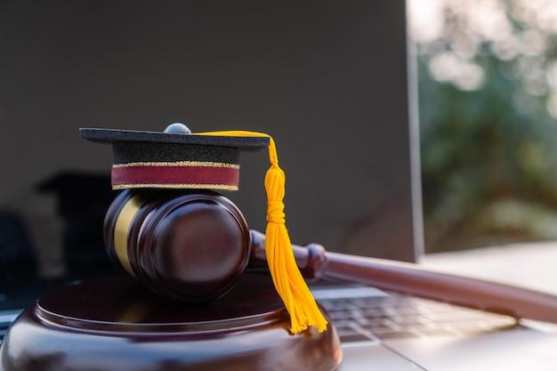 Concept van afgestudeerde online studie internationaal in het buitenland over jurisprudentiewetten certificaat in universitair afstandsonderwijs om te leren. afstuderen diploma hoed/rechter hamer op computer notebook.