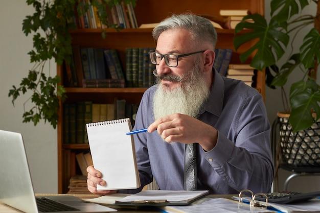 Concept van afstandsonderwijs. leraar, vertaler, tutor op het bureaublad in de bibliotheek wijst met pen op lege plaat