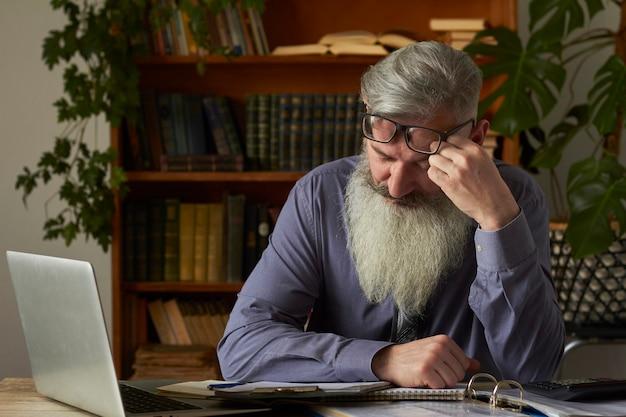 Concept van afstandsonderwijs. moe van streek leraar tutor kijken naar laptop en masseert de tempel
