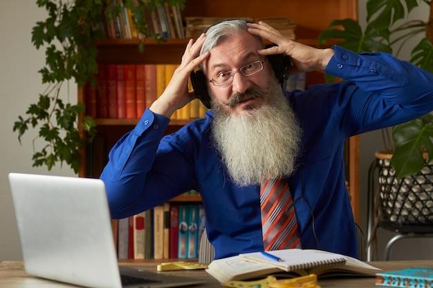 Concept van afstandsonderwijs. waanzinnige lerarenleraar die naar laptop kijkt en zijn hoofd vasthoudt