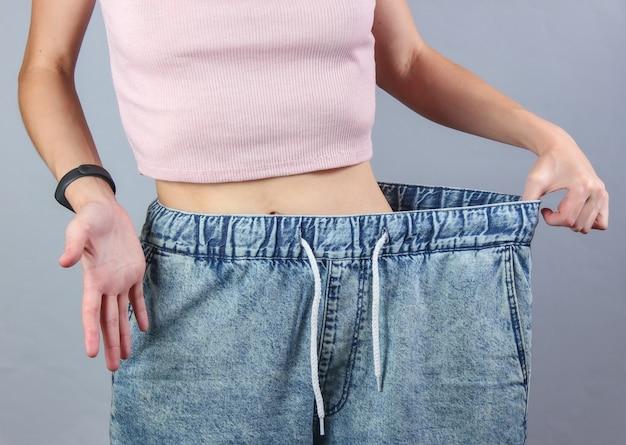 Concept van afvallen. vrouw in zeer grote jeans op grijze studioachtergrond.