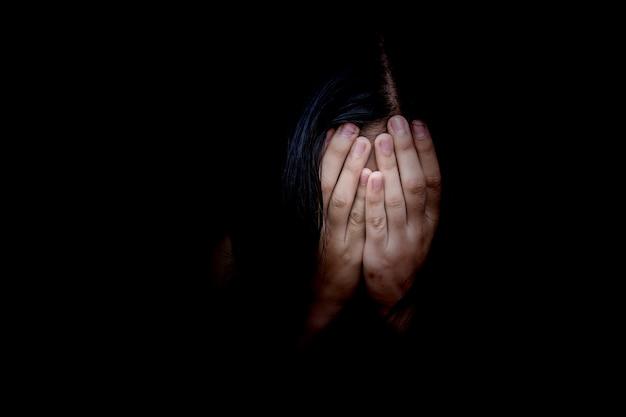 Concept van angst, huiselijk geweld. de vrouw behandelt haar gezicht haar handen