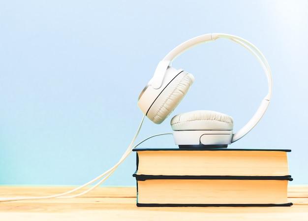 Concept van audioboek. boeken op tafel met een koptelefoon erop