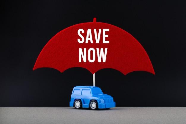 Concept van autoverzekering. blauwe auto onder rode paraplu met tekst nu opslaan.