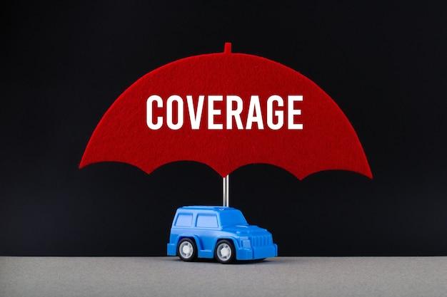 Concept van autoverzekering. blauwe auto onder rode paraplu met tekstdekking.