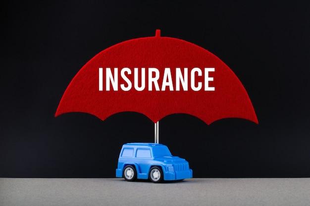 Concept van autoverzekering. blauwe auto onder rode paraplu met tekstverzekering.