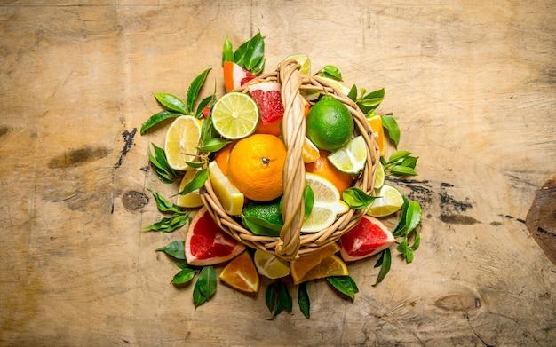 Concept van citrus. mand met citrusvruchten. grapefruit, sinaasappel, mandarijn, citroen, limoen op houten tafel. bovenaanzicht