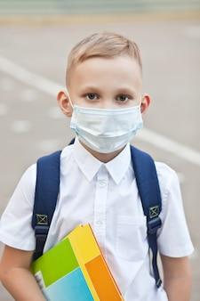 Concept van coronavirus covid-19. schooljongen die een medisch gezichtsmasker draagt om de gezondheid te beschermen tegen het griepvirus