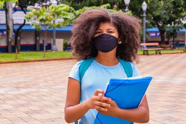 Concept van coronavirus covid-19. schoolmeisje dat een medisch gezichtsmasker draagt om de gezondheid te beschermen tegen het griepvirus. studentenmeisje met rugzak en boeken - in openlucht portret. kind terug naar school.