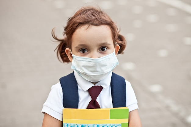 Concept van coronavirus covid-19. schoolmeisje dat een medisch gezichtsmasker draagt om de gezondheid te beschermen tegen het griepvirus.