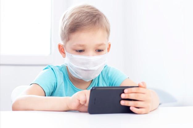 Concept van coronavirus-infectie. jongen in een medisch masker zit binnenshuis op een stoel en speelt een gadget.