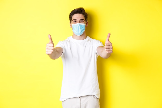 Concept van coronavirus, pandemie en sociale afstand. zelfverzekerde man die zichzelf beschermt tegen covid-19 met medisch masker, duimen opdagend ter goedkeuring, gele achtergrond