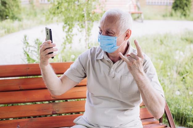 Concept van coronavirus quarantaine, coronavirus, man met medische gezichtsmasker met behulp van de telefoon om selfie te maken. luchtvervuiling