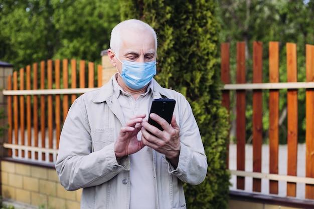 Concept van coronavirus quarantaine, coronavirus, man met medische gezichtsmasker met behulp van de telefoon om te zoeken naar nieuws. luchtvervuiling