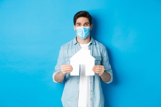 Concept van coronavirus, quarantaine en sociale afstand. jonge man zoekt appartement, toont huispapieren model, draagt een medisch masker, huurt of koopt onroerend goed, blauwe achtergrond.