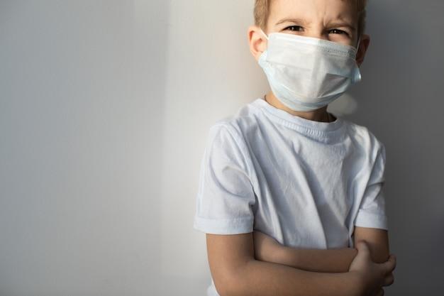 Concept van coronavirus quarantaine. mers-cov, novel coronavirus (2019-ncov), jongen met medisch gezichtsmasker. gezondheid en medicijnen.