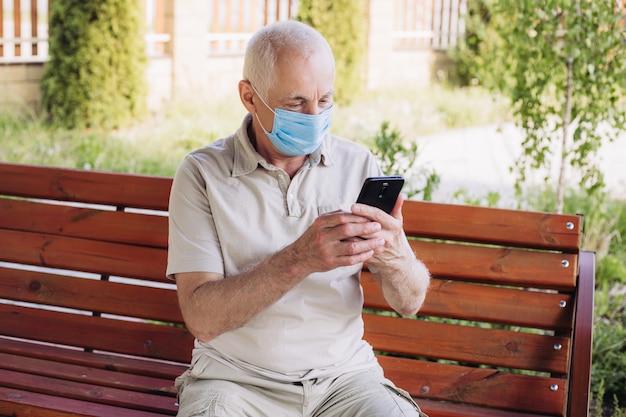 Concept van coronavirus quarantaine. senior man met medische gezichtsmasker met behulp van de telefoon naar nieuws te zoeken. luchtvervuiling