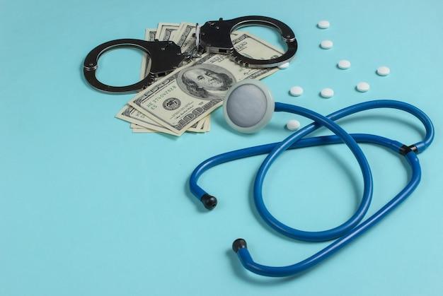 Concept van corruptie in de geneeskunde. stethoscoop, pillen en handboeien met honderd dollarbiljetten op blauwe achtergrond. medisch stilleven. straf voor misdaad