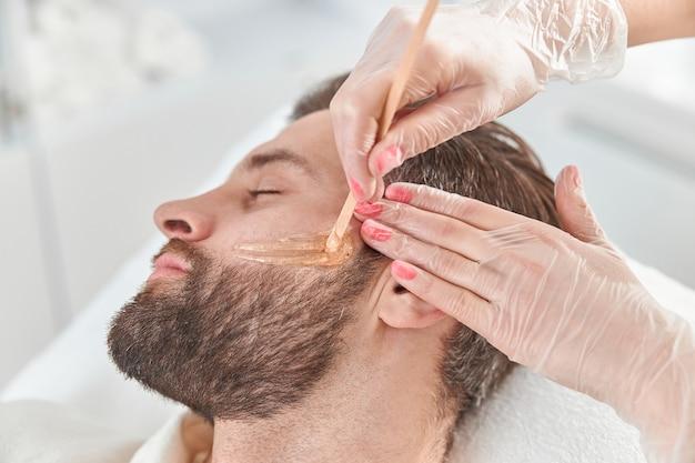 Concept van cosmetologie en gezichtsbehandeling. een vrouwelijke schoonheidsspecialiste maakt gezichts- en baardmodellering voor een harige epilatie van een man. ontharen met was.