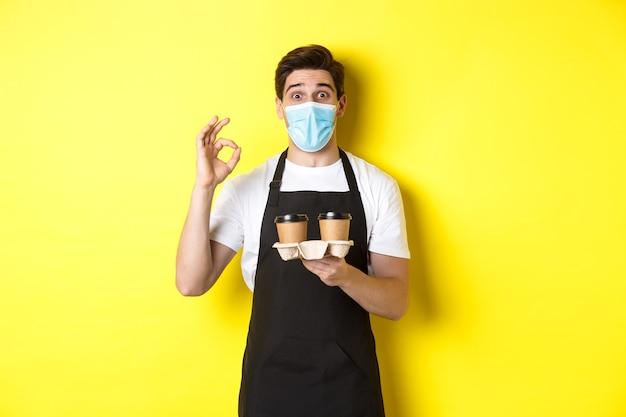 Concept van covid-19, café en sociaal afstand nemen. barista in medisch masker en zwarte schort garanderen veiligheid, houden afhaalkoppen koffie vast en tonen ok-teken, gele achtergrond.
