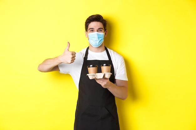 Concept van covid-19, café en sociaal afstand nemen. jonge mannelijke barista in medisch masker en zwarte schort met afhaalmaaltijden koffiekopjes, duim opdagen, gele achtergrond.