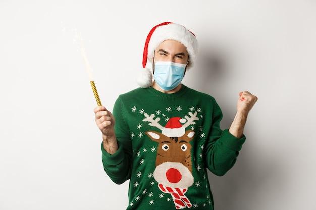 Concept van covid-19 en kerstvakantie. gelukkige jonge man in gezichtsmasker die kerstmis viert, feeststerretje vasthoudt en zich verheugt, staande op een witte achtergrond.
