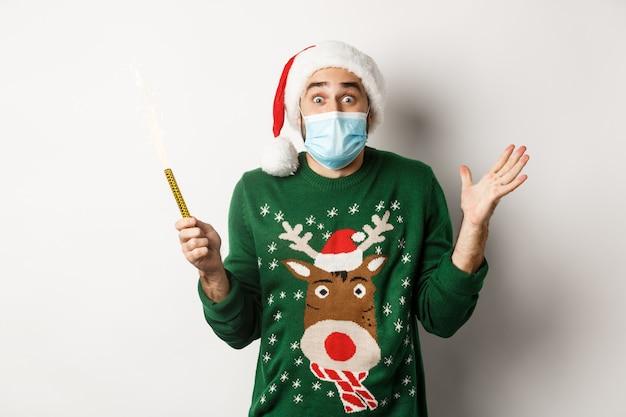 Concept van covid-19 en kerstvakantie. gelukkige jonge man met gezichtsmasker die kerstmis viert, feeststerretje vasthoudt en zich verheugt, staande op een witte achtergrond