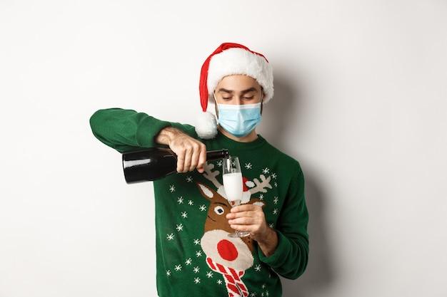 Concept van covid-19 en kerstvakantie. gelukkige kerel in gezichtsmasker en kerstmuts, nieuwjaarsfeest vieren en glas champagne gieten, witte achtergrond