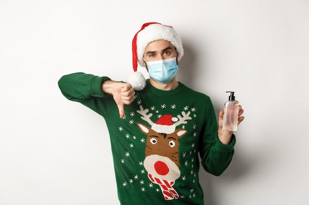 Concept van covid-19 en kerstvakantie met knappe jonge man met een masker
