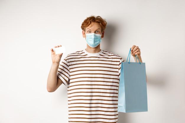 Concept van covid-19 en levensstijl. vrolijke jonge man met rood haar, draag een medisch masker, met boodschappentas uit de winkel en plastic creditcard.
