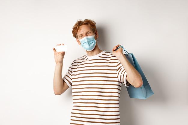 Concept van covid-19 en levensstijl. vrolijke jonge man met rood haar, draag medisch masker, boodschappentas uit winkel en plastic creditcard te tonen.