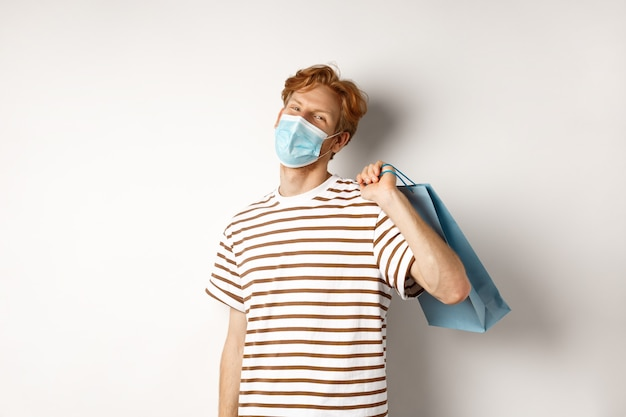 Concept van covid-19 en winkelen. tevreden jonge man die tevreden is na het winkelen, gezichtsmasker draagt, papieren zak vasthoudt en glimlacht, witte achtergrond.