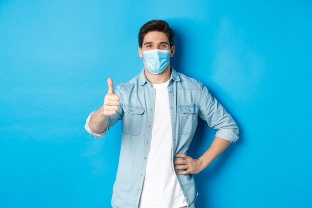 Concept van covid-19, pandemie en sociale afstand. tevreden man met medisch masker die zijn duim in goedkeuring laat zien, staande tegen een blauwe achtergrond