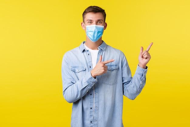 Concept van covid-19 pandemische uitbraak, levensstijl tijdens sociale afstand van het coronavirus. blije gelukkige knappe man, glimlachend in medisch masker en wijzend rechterbovenhoek op advertentie.